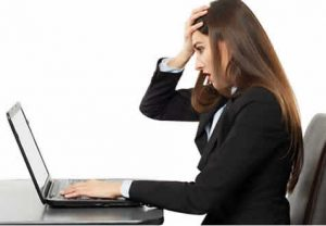 Girl with hand on head having read something defaming on laptop