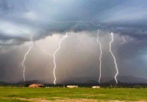 Lightening over field of cattle